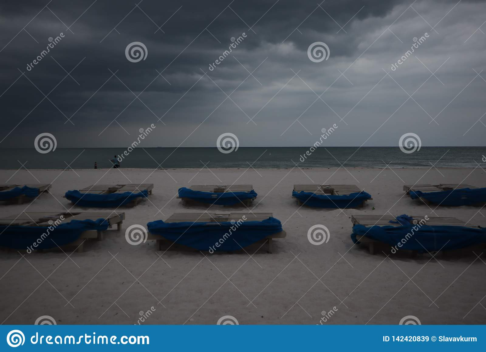 Sunbeds met blauwe handdoeken op een zandig strand in stormachtig weer grijze donderwolken