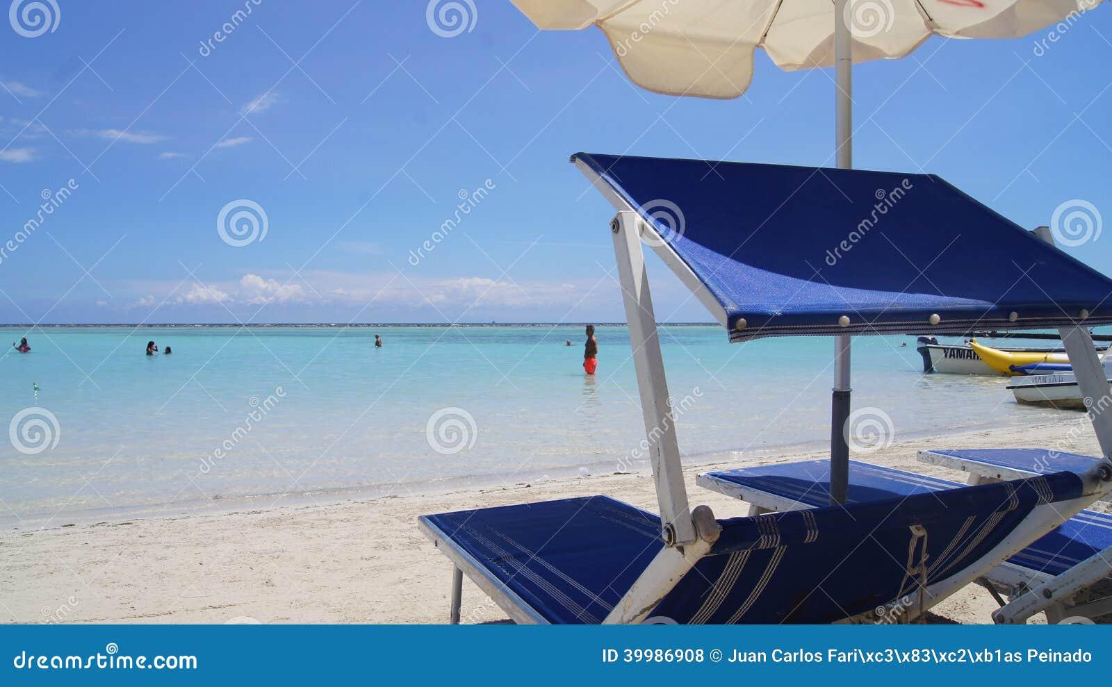 Sunbeds och paraplyer på stranden av Boca Chica,
