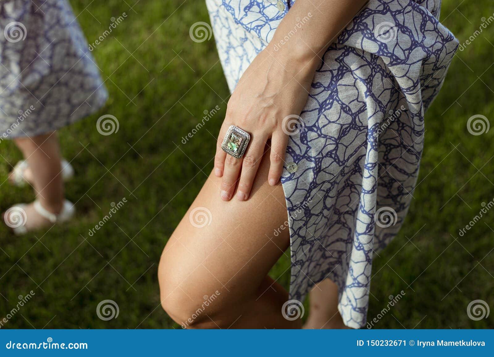 Sunburnt women legs in summer cloth and hand