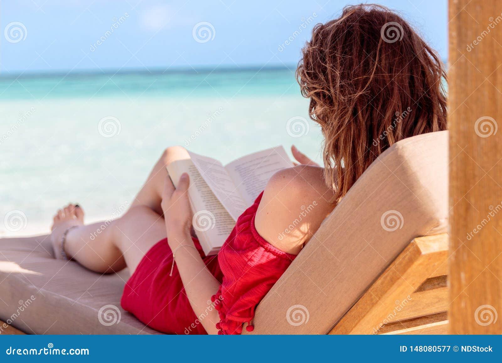 Sunchair的妇女读一本书的在一个热带地点 作为背景的清楚的绿松石水