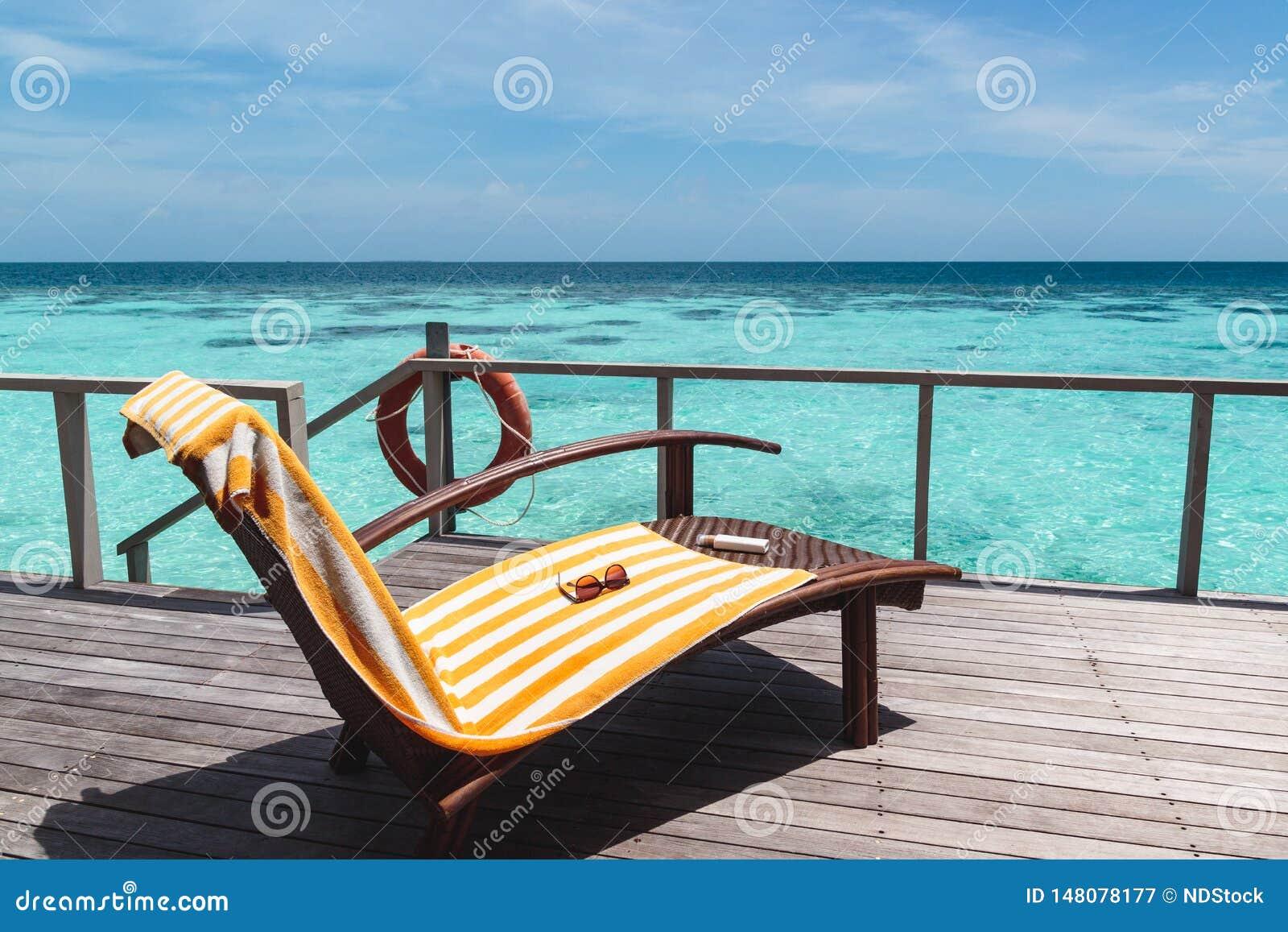 Sunchair com toalha em um terraço sobre a água azul clara durante um dia ensolarado