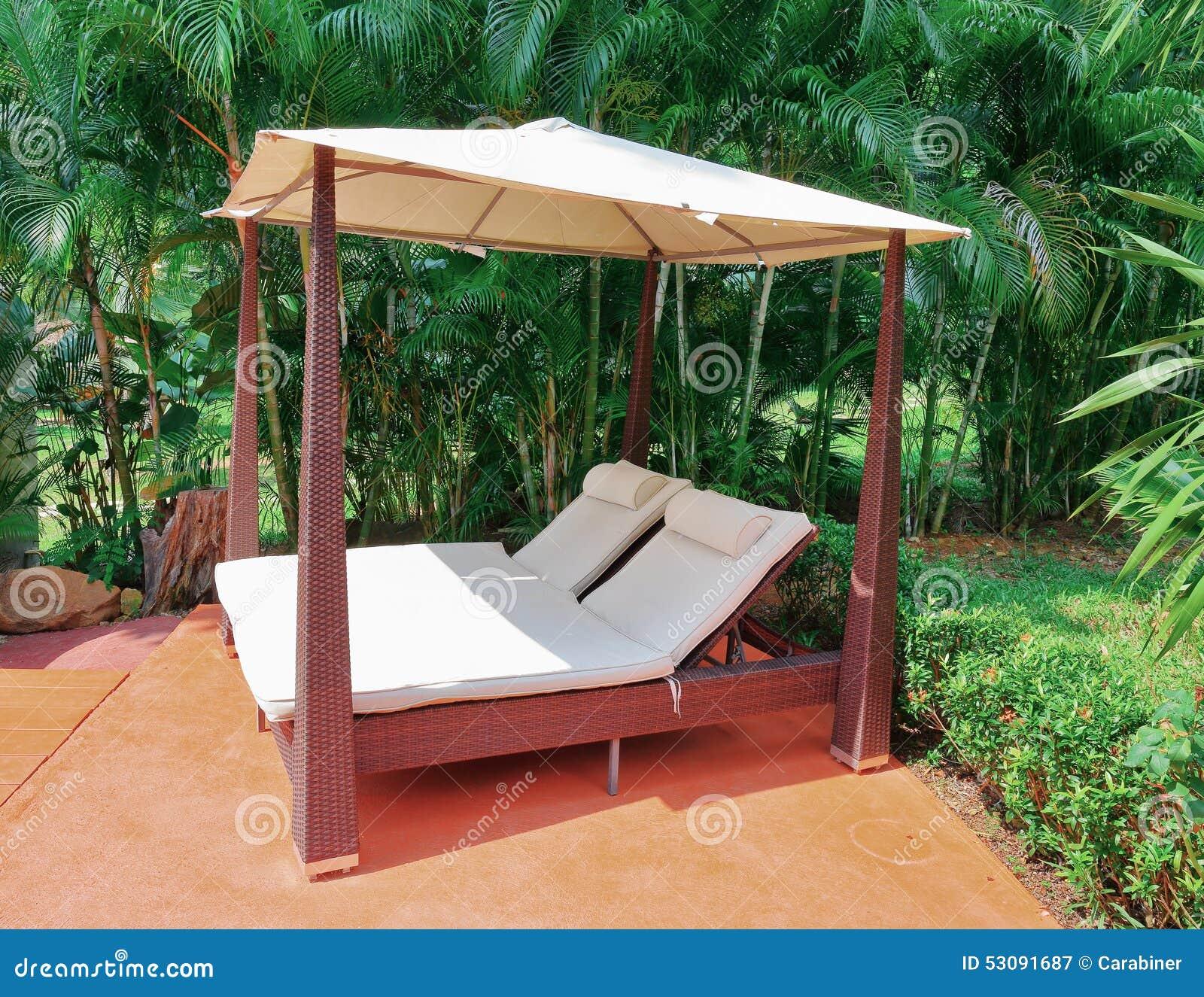 sunchairs unter sonnenschutz im garten stockbild - bild von ferien