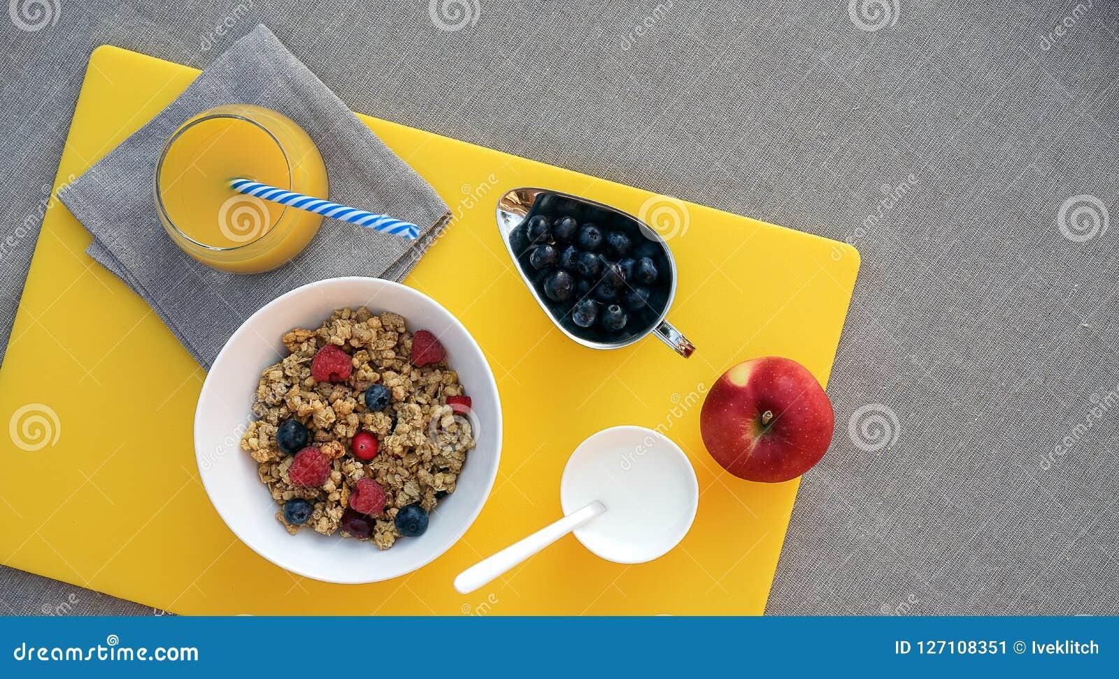 Sund frukost med granola, grekisk yoghurt, äpplet, bär och ny orange fruktsaft på gul skärbräda på grå bordduk