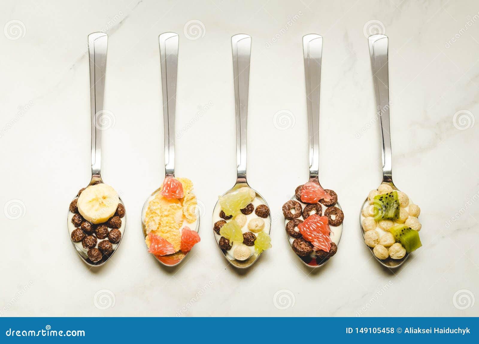 Sund frukostyoghurt, flingor och frukt i skedar B?sta sikt som ?r flatlay