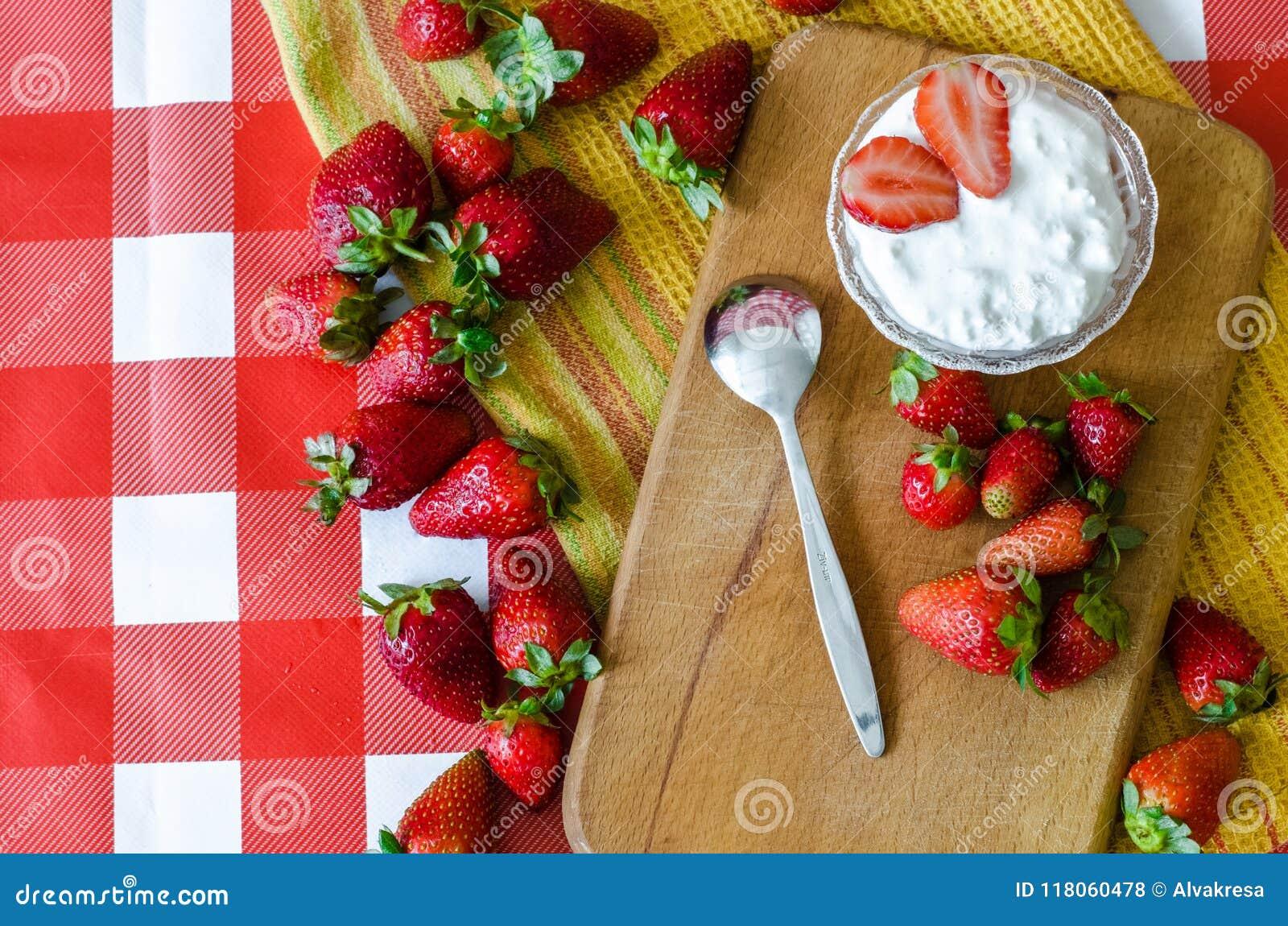Sund frukt som är mest breakfest med ny yoghurt i liten glass bunke, mogna jordgubbar och efterrättsked