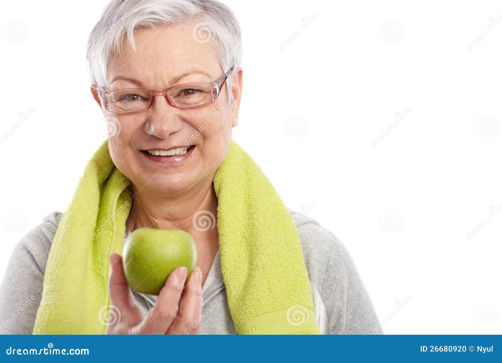 Sund gammal kvinna med grönt le för äpple