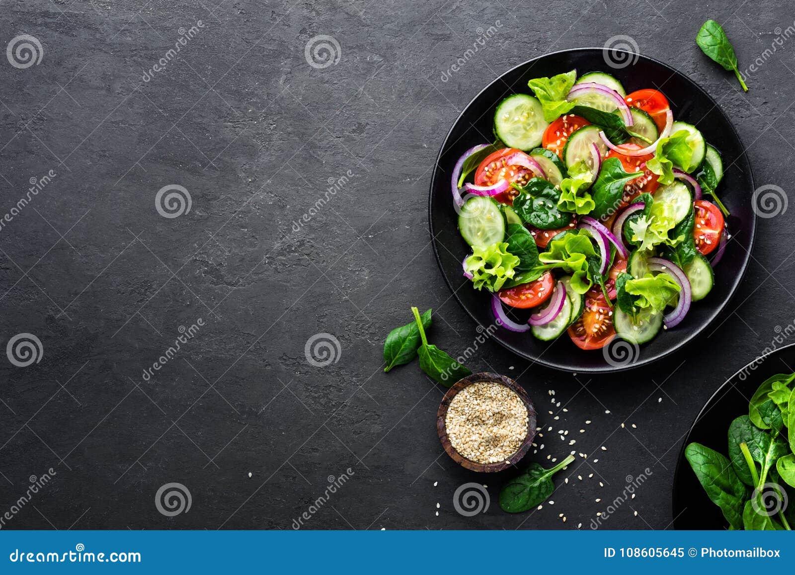 Sund grönsaksallad av den ny tomaten, gurkan, löken, spenat, grönsallat och sesam på plattan Banta menyn