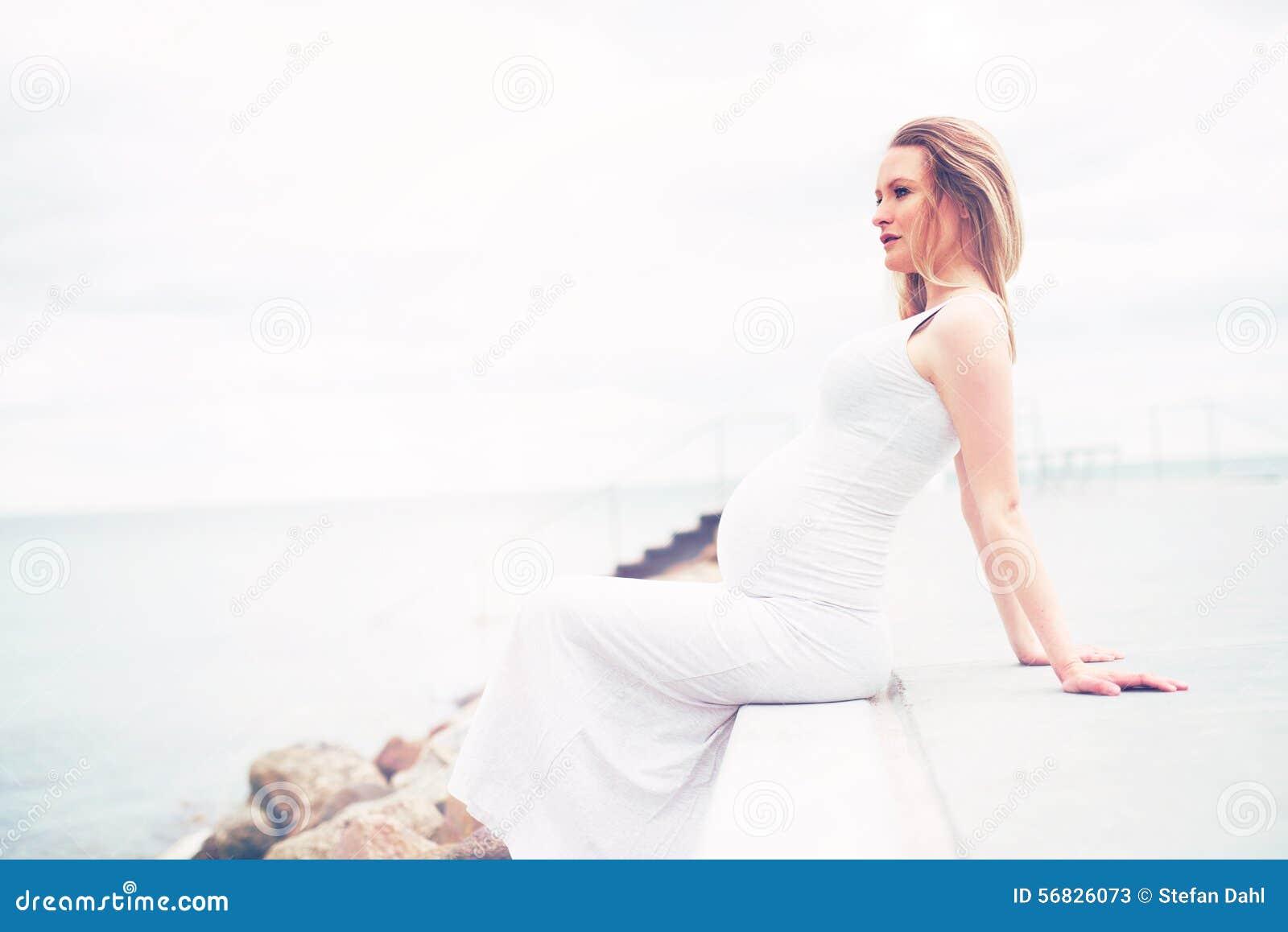 Sund gravid kvinna som kopplar av på sjösidan