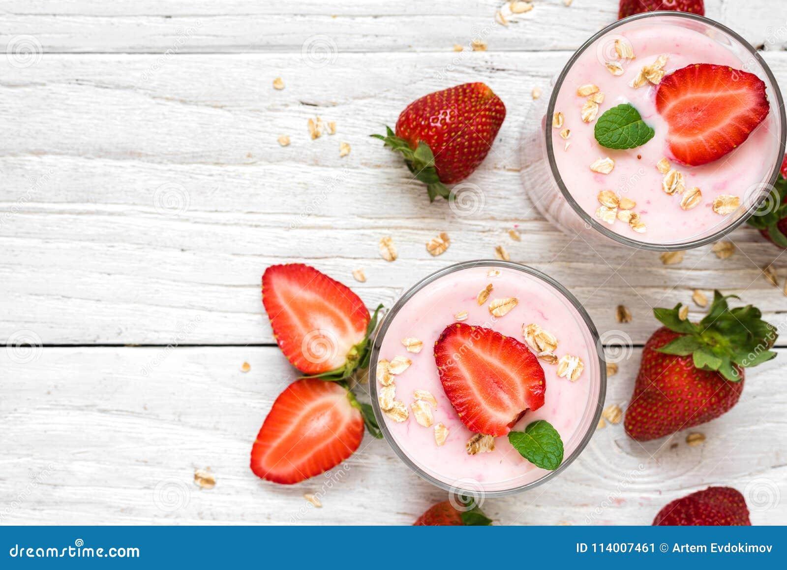 Sund jordgubbeyoghurt med havre och mintkaramellen i exponeringsglas med nya bär över den vita trätabellen