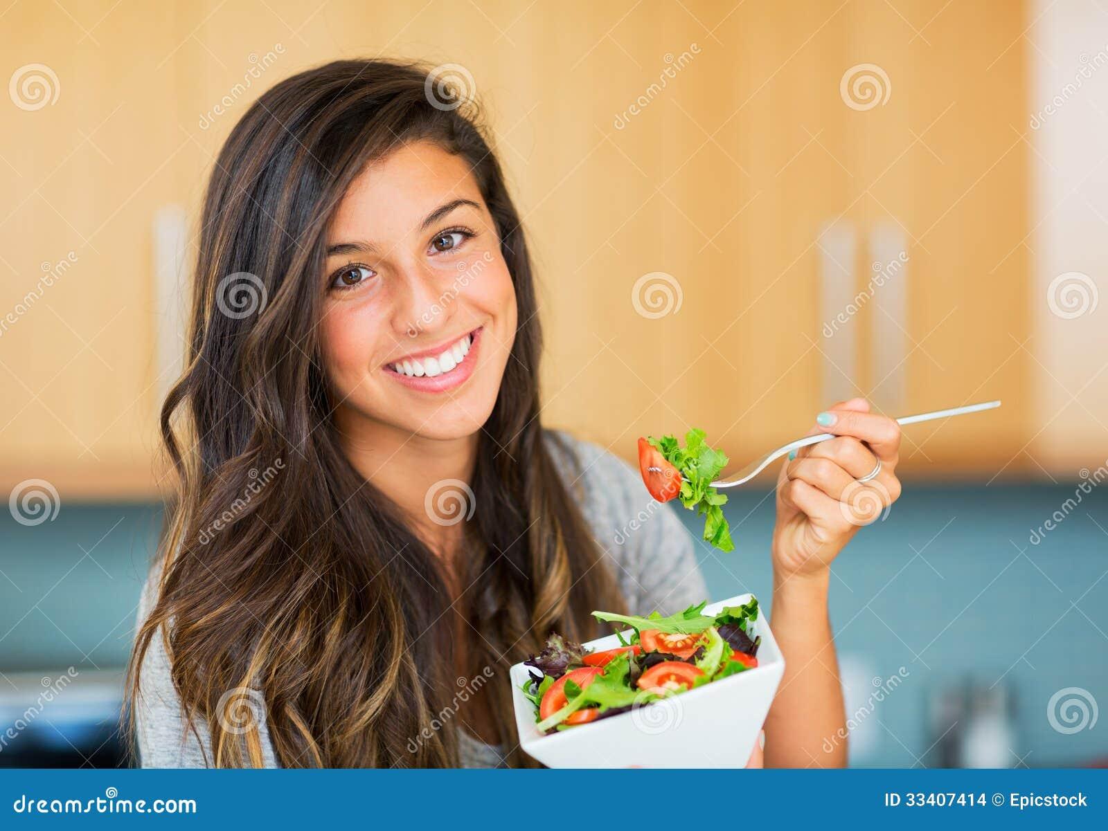 Sund kvinna som äter sallad