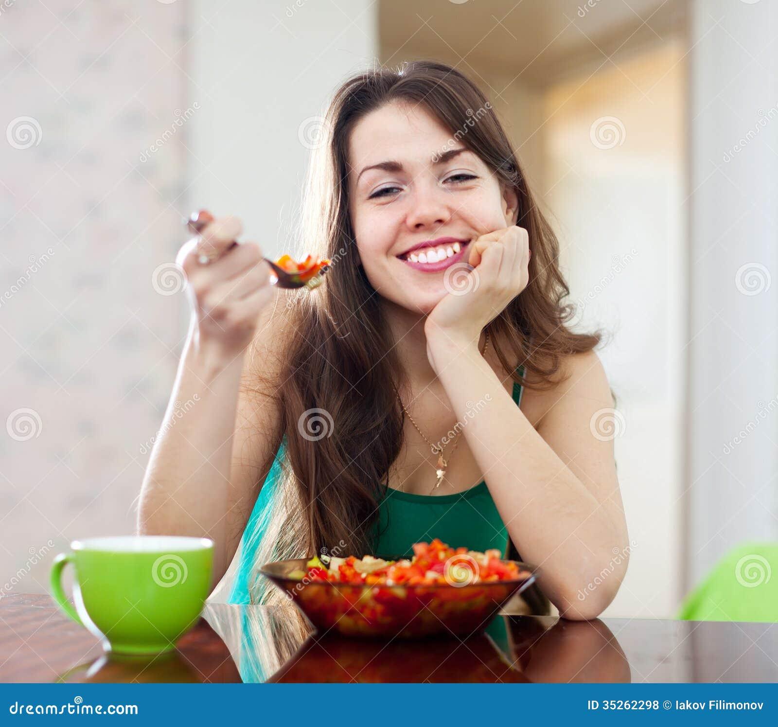 Sund kvinna som äter veggiesallad