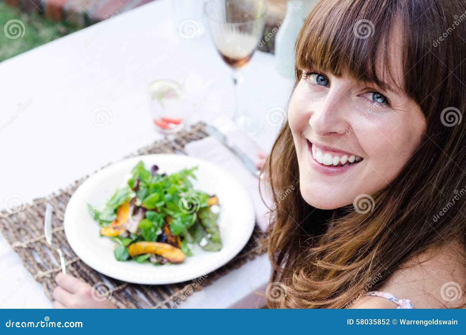 Sund kvinna som utomhus äter sallad