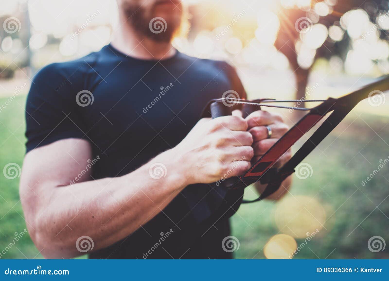 Sund livsstil för begrepp Den muskulösa idrottsman nen som övar trx, skjuter utanför i soligt parkerar upp Färdig shirtless manli