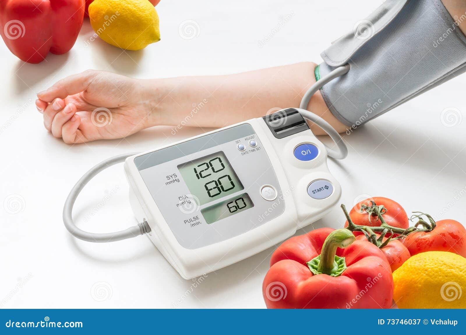Sund livsstil för begrepp Kvinnan mäter blodtryck med bildskärmen