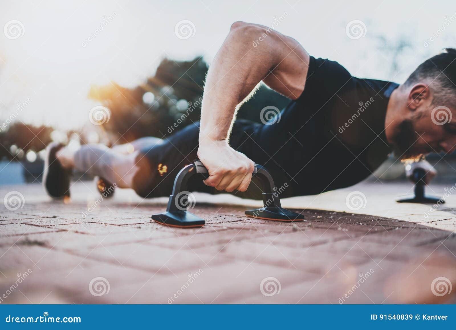 Sund livsstil för begrepp utomhus utbilda Stilig sportidrottsman nenman som gör liggande armhävningar i parkera på den soliga mor