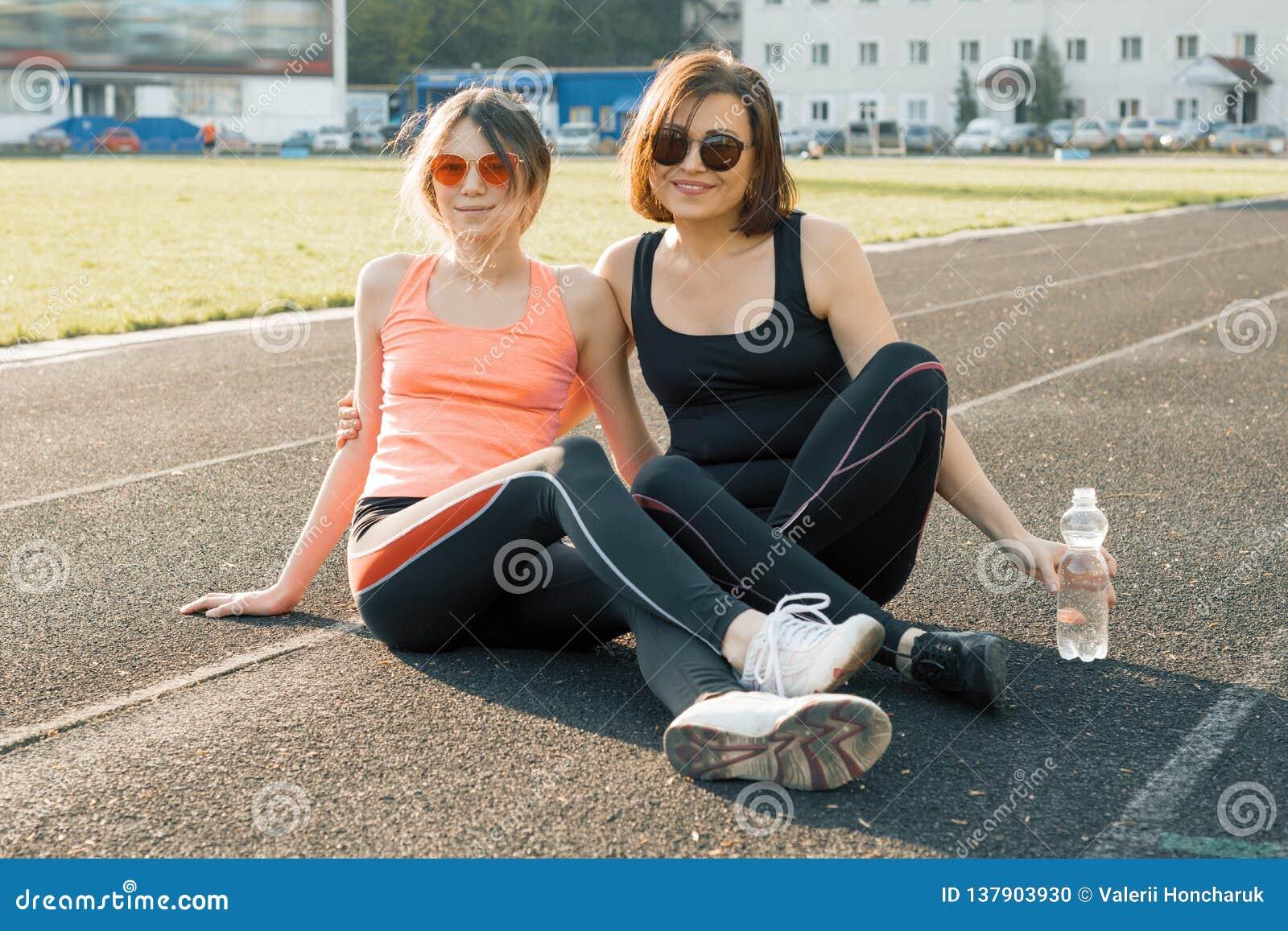 Sund livsstil, sund familj Le konditionmodern och den tonåriga dottern som poserar tillsammans på stadion, når att ha kört på sol