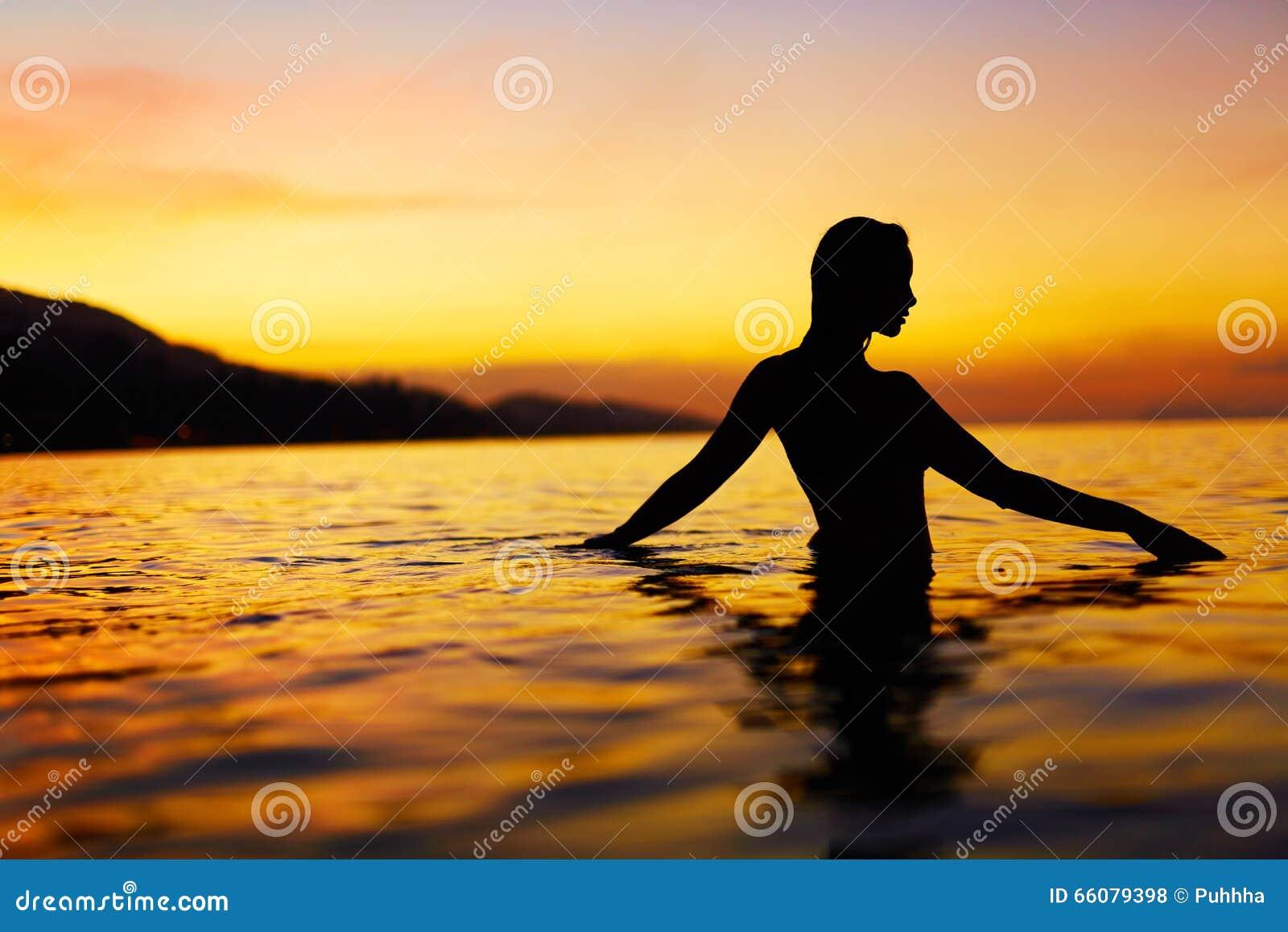 Sund livsstil, hälsa Kvinna som tycker om havssolnedgång Sommar vac