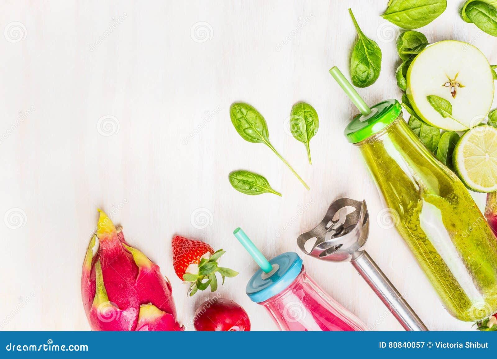Sund mat med rosa färg- och gräsplansmoothies i flaskor med sugrör och ingredienser: äpple limefrukt, spenat, jordgubbar, plommon