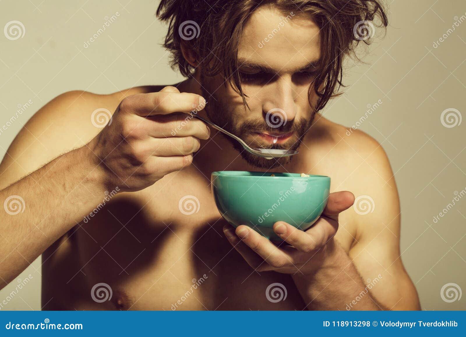 Sund mat och banta, kondition, morgon mannen med den kala bröstkorgen som äter frukosten av havremjölet med, mjölkar
