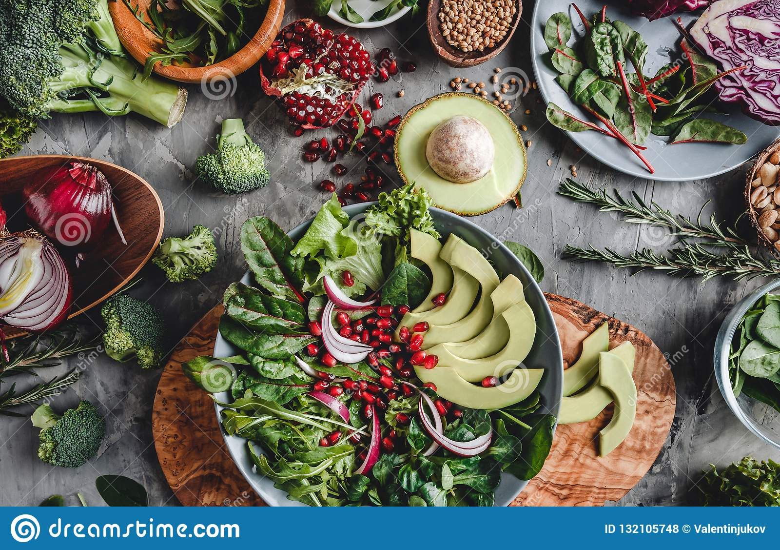Sund ny sallad med avokadot, gräsplaner, arugula, spenat, granatäpple i platta över grå bakgrund Sund strikt vegetarianmat,