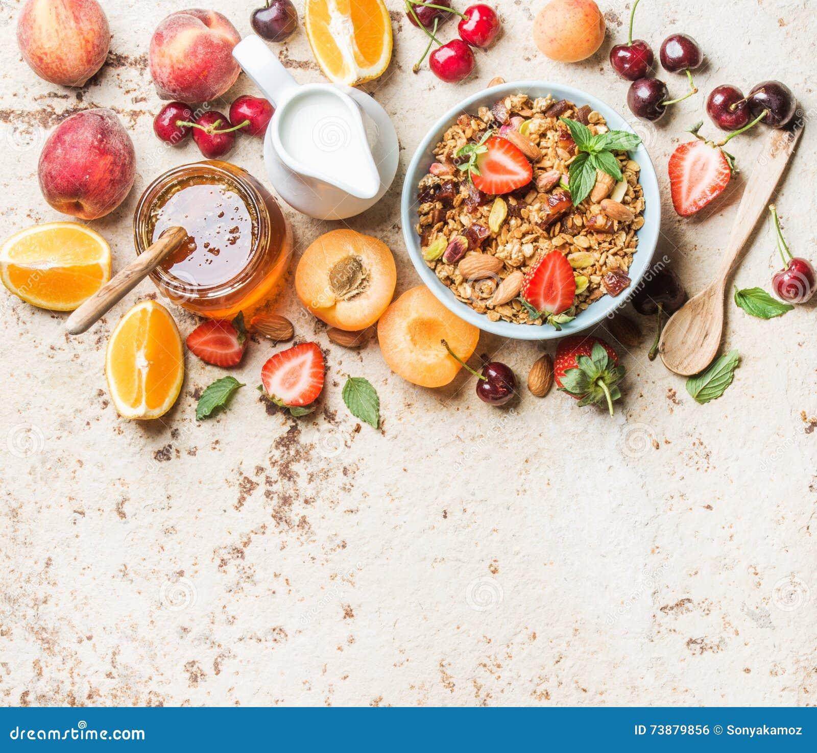 Sunda frukostingredienser Havregranola i bunke med muttrar, jordgubbe och mintkaramell, mjölkar i tillbringaren, honung i den gla