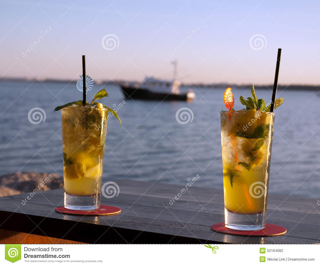 Sundowner cocktails with blurred boat