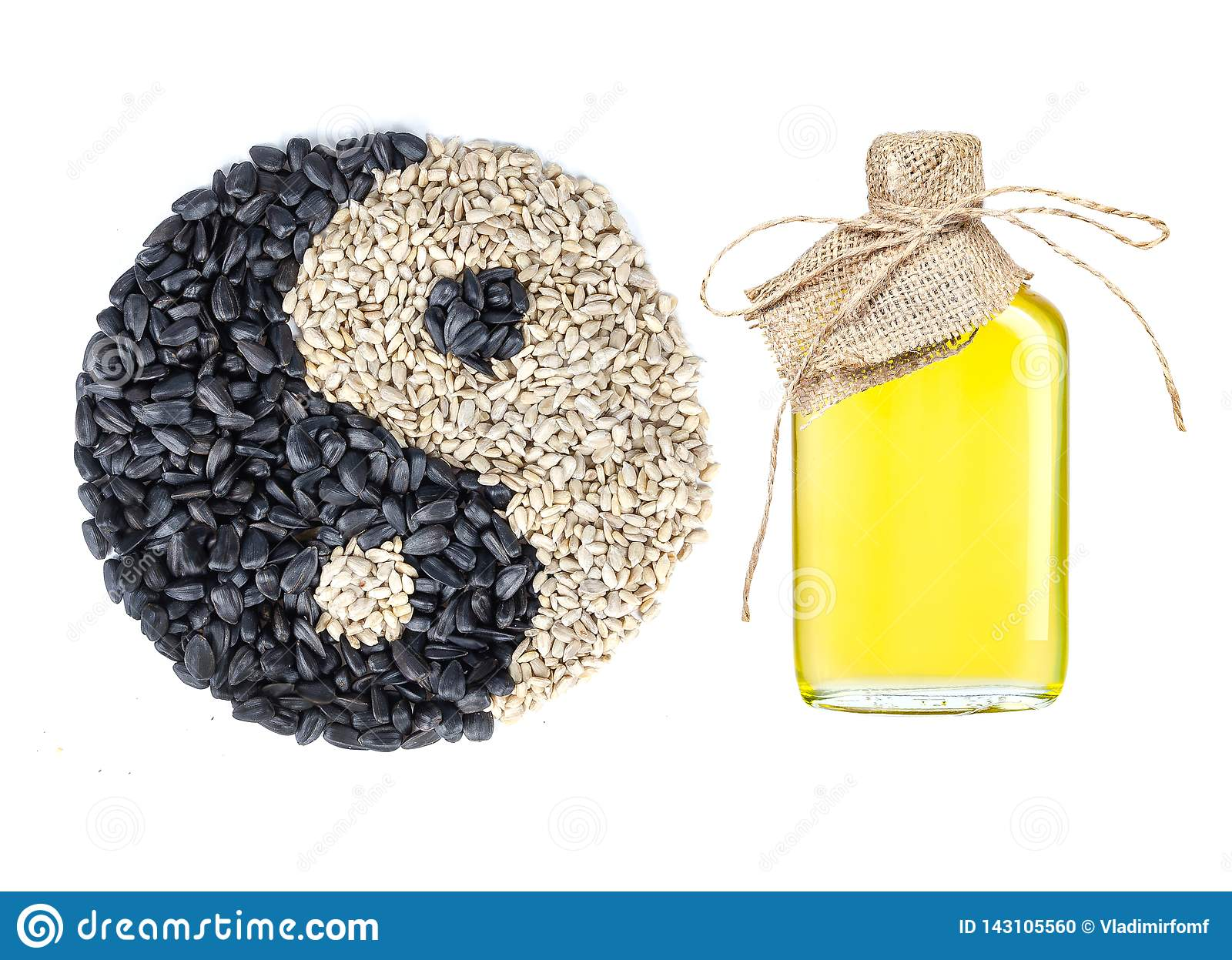 Sunflower oil in a crafted glass bottle and an yin and yang symbol made of seeds on white backgound