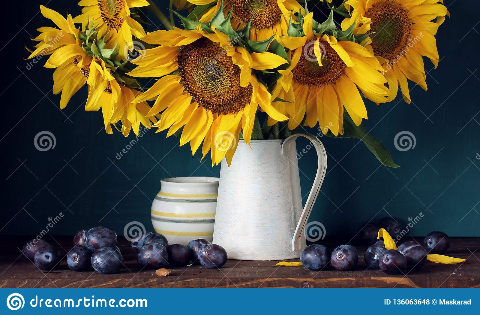 Sunflowers and purple plums. flowers and fruit