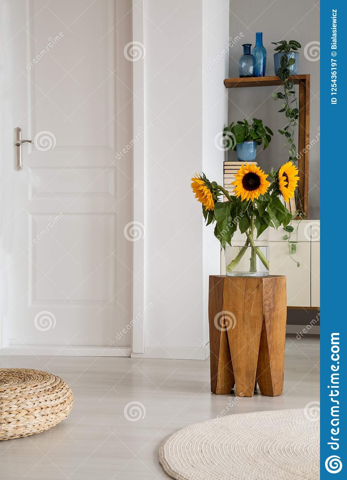 Sunflowers on wooden stool next to pouf in white living room interior with door and rug. Real photo