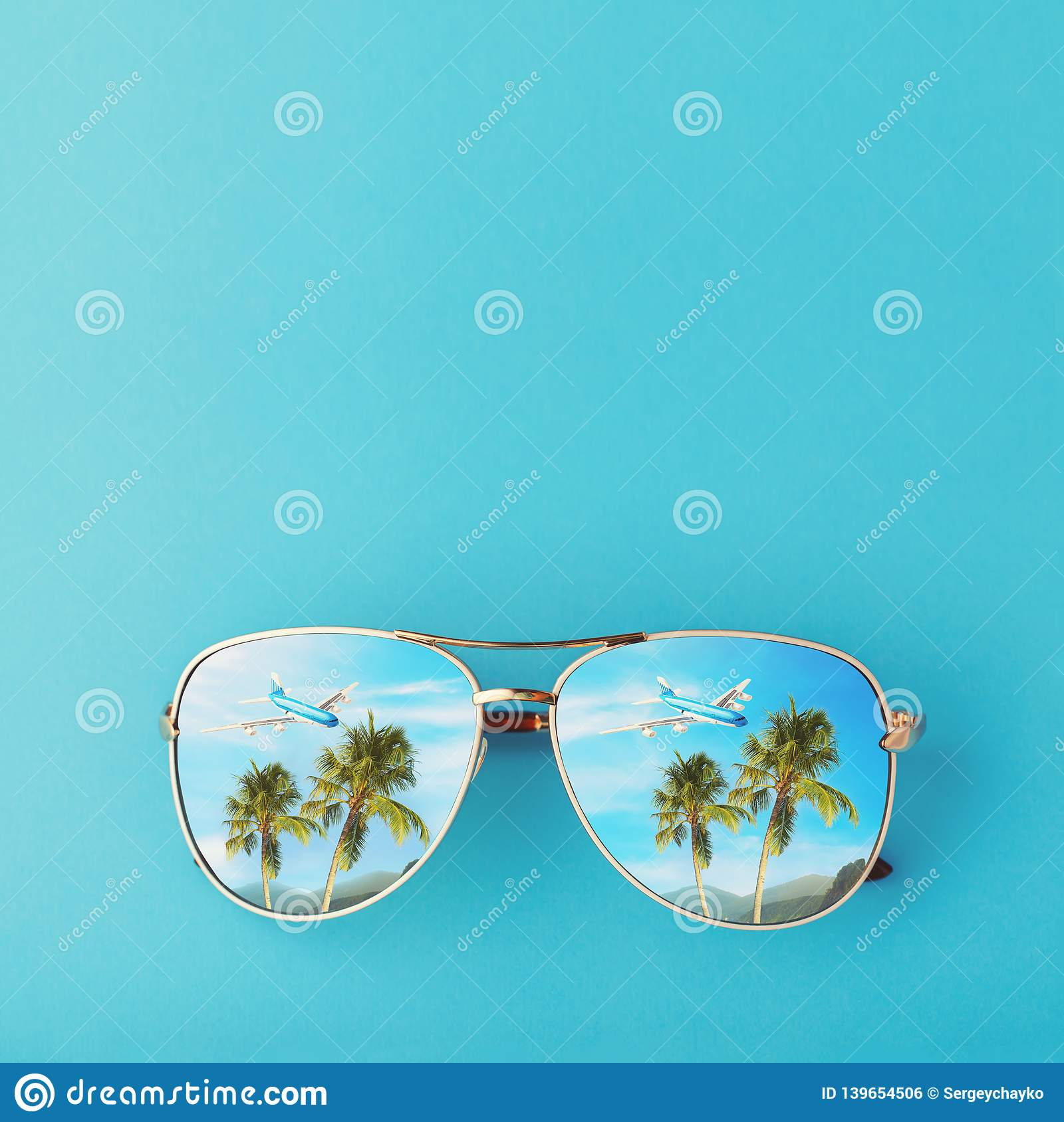 Sunglasses with palm trees, a plane and mountains reflected in them. Concept on the theme of vacation and travel with copy space