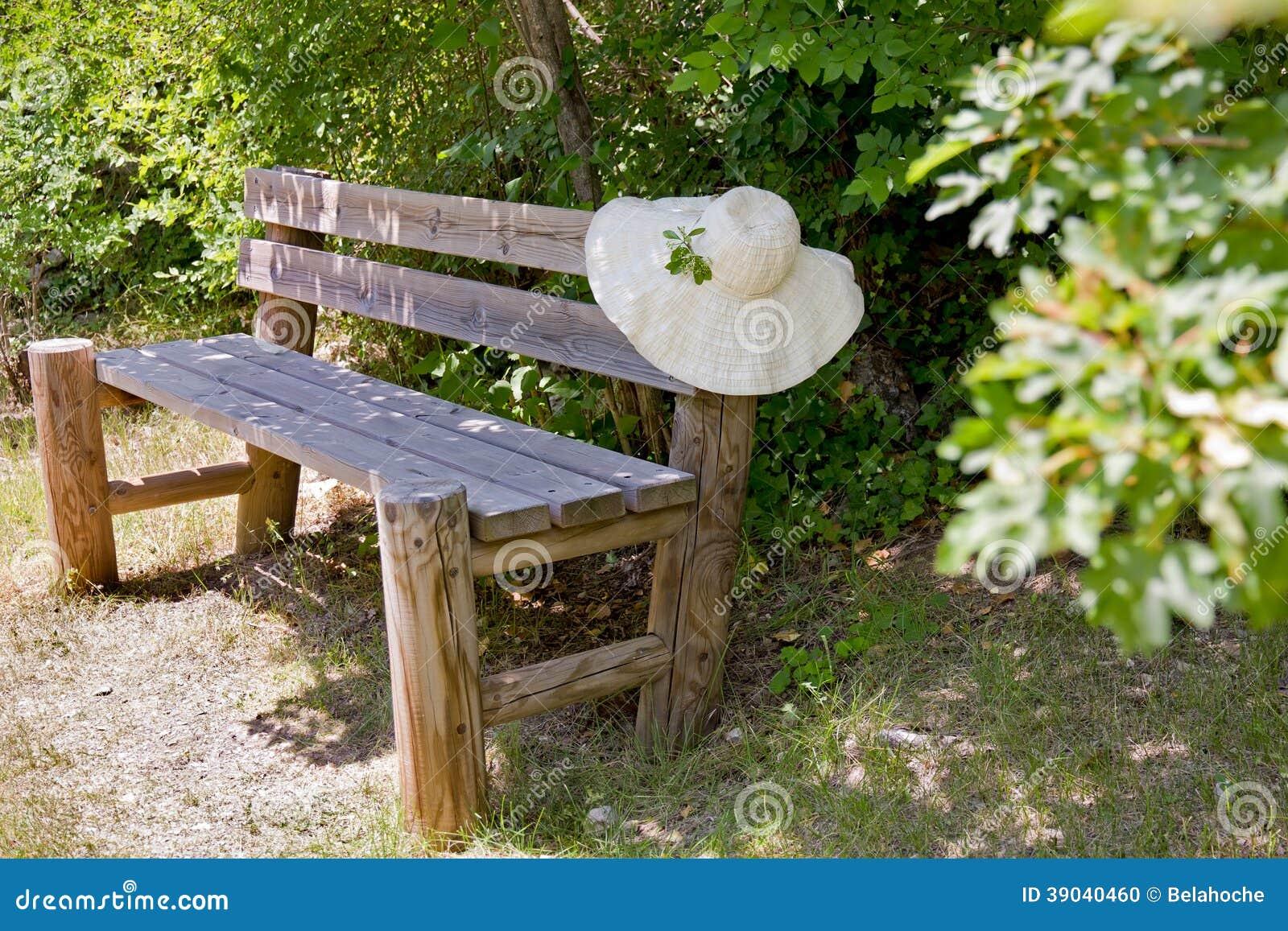Sunhat en un banco de madera del jardín.