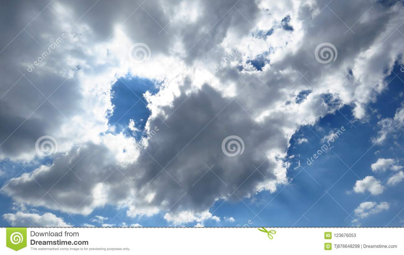 Sunlight coming through clearing storm white and grey clouds, blue sky. Weather forecast concept. Oxygen, environment.