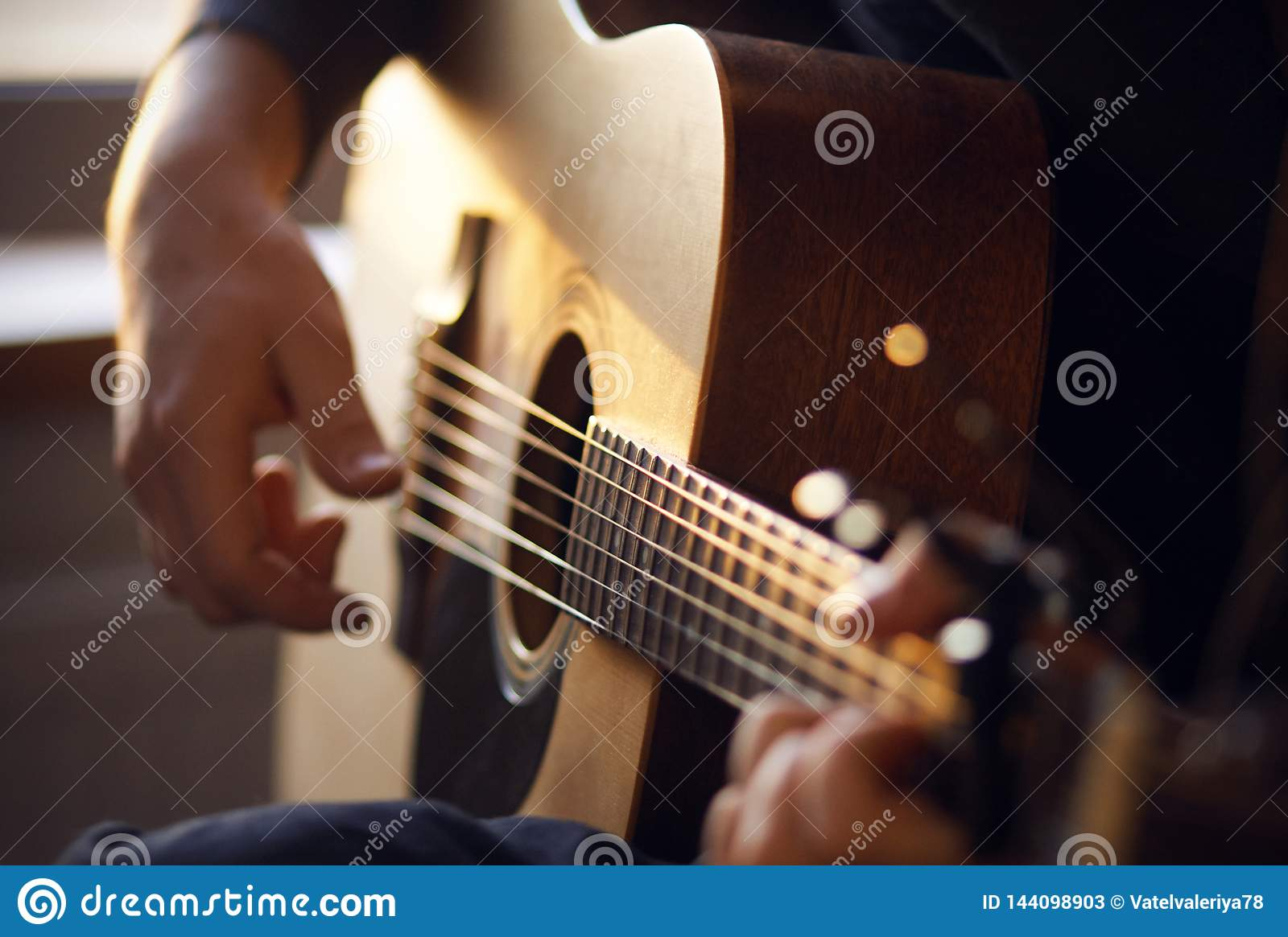 Sunlight illuminates the guitarist, playing a melody on a guitar
