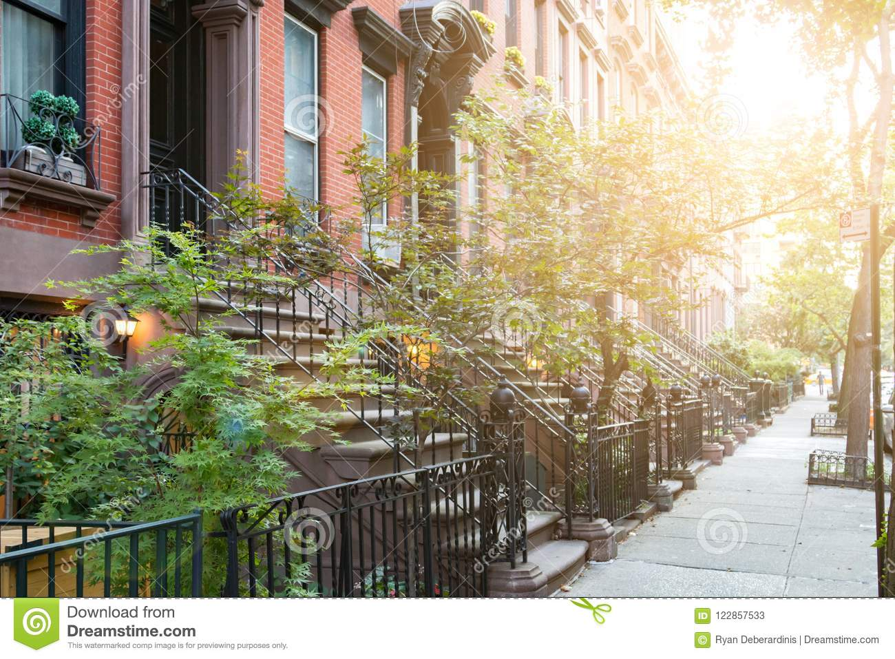 Sunlight shines on historic brownstone buildings in New York City