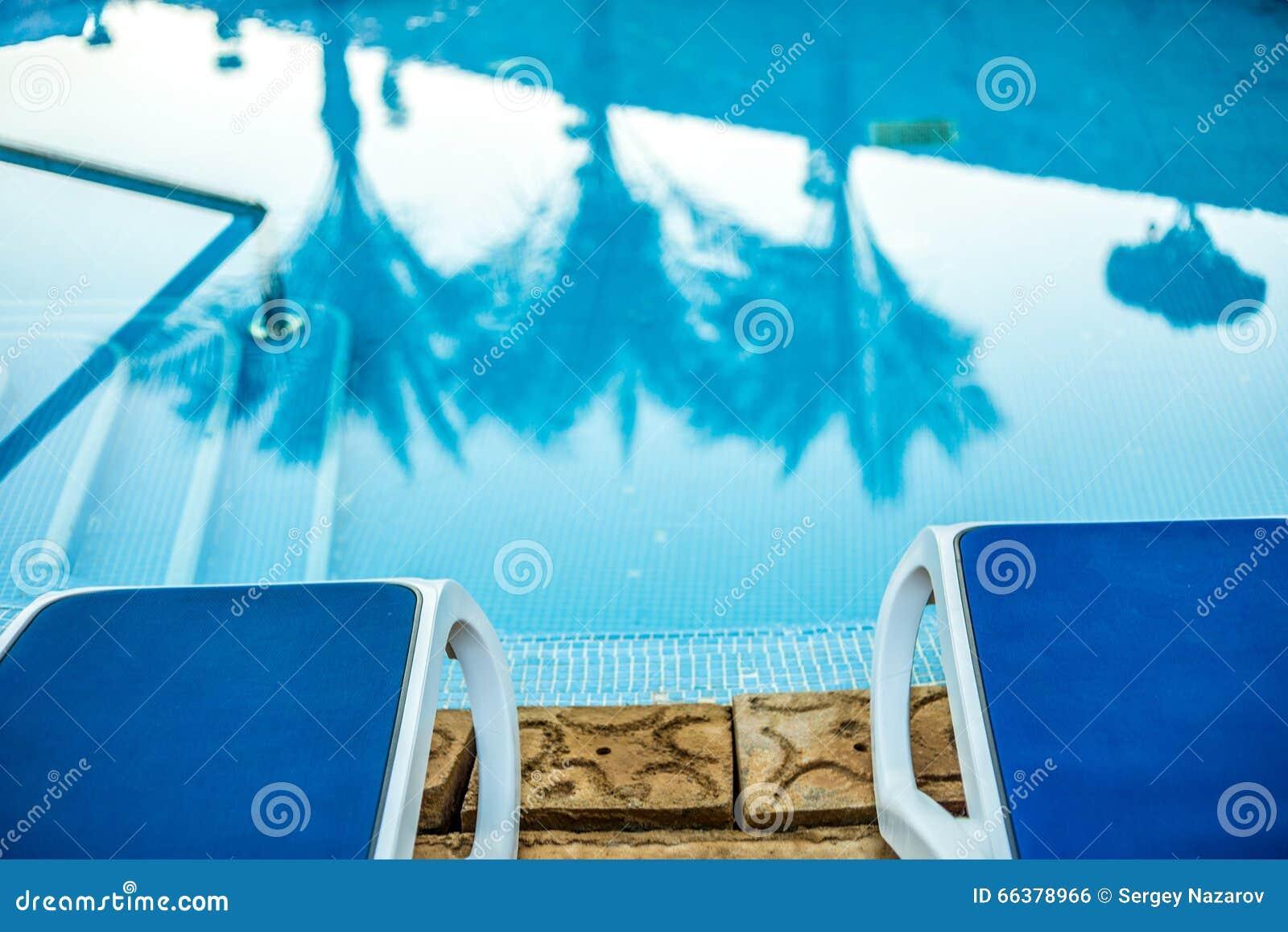Sunloungers e piscina del primo piano con le palme for Disposizione del piano piscina