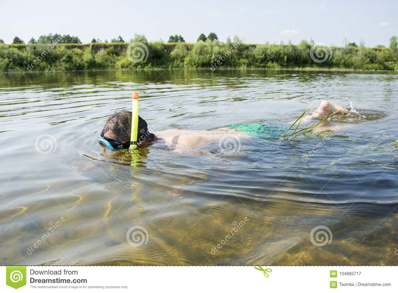 In summer, a man in a mask and a tube in clear water swim along
