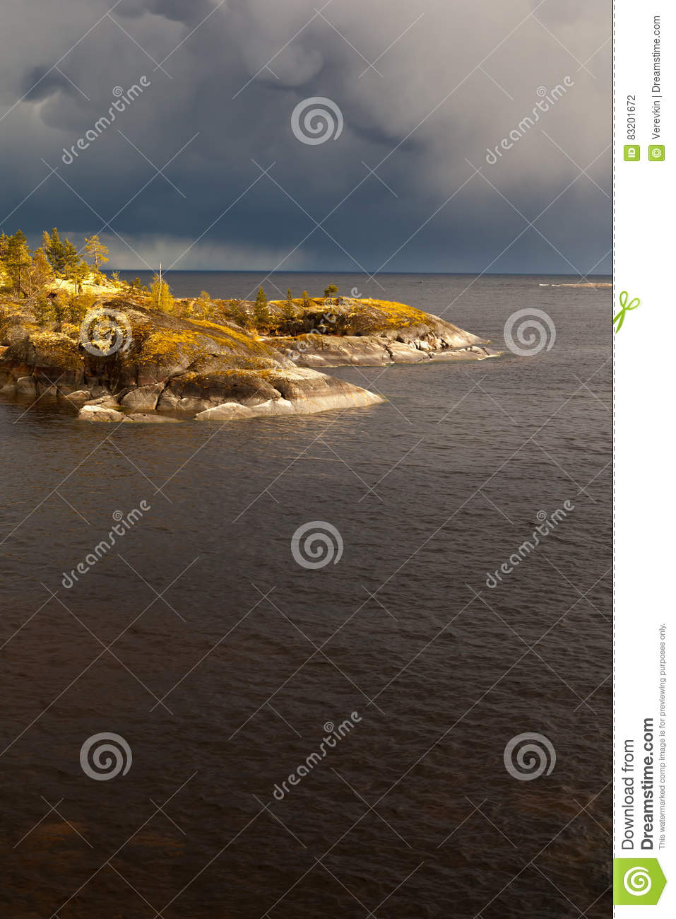 Sunny day on the rocky shore of the lake.
