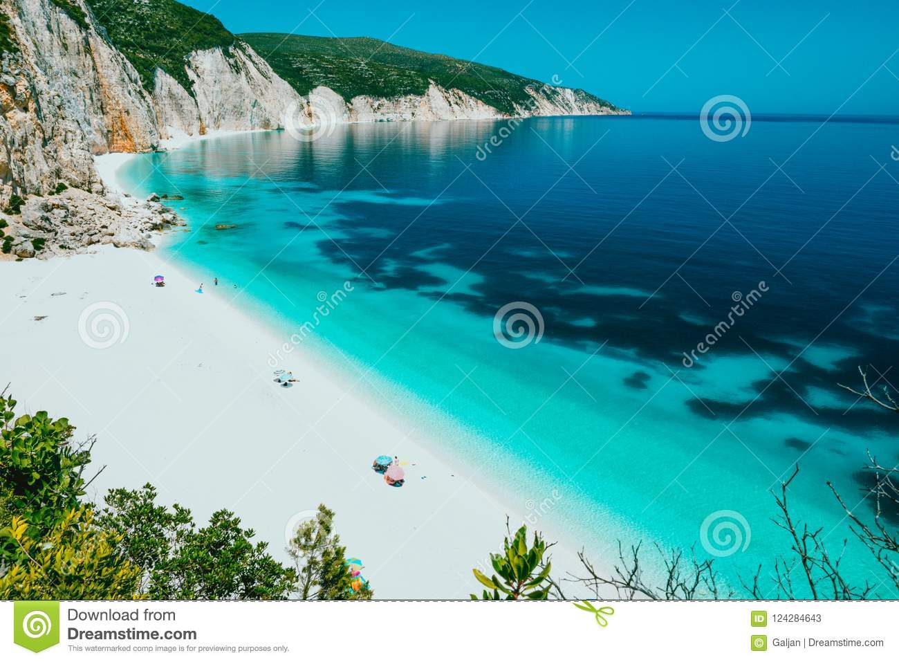Sunny Fteri beach lagoon with rocky coastline, Kefalonia, Greece. Tourists under umbrella chill relax near clear blue