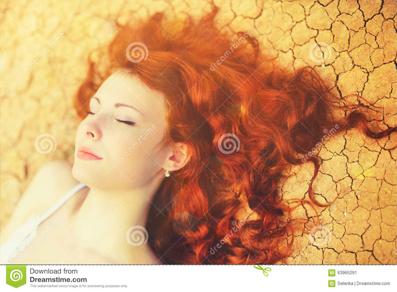 Sunny portrait of a relaxing young woman with chic long curly red hair lying on the cracked ground.