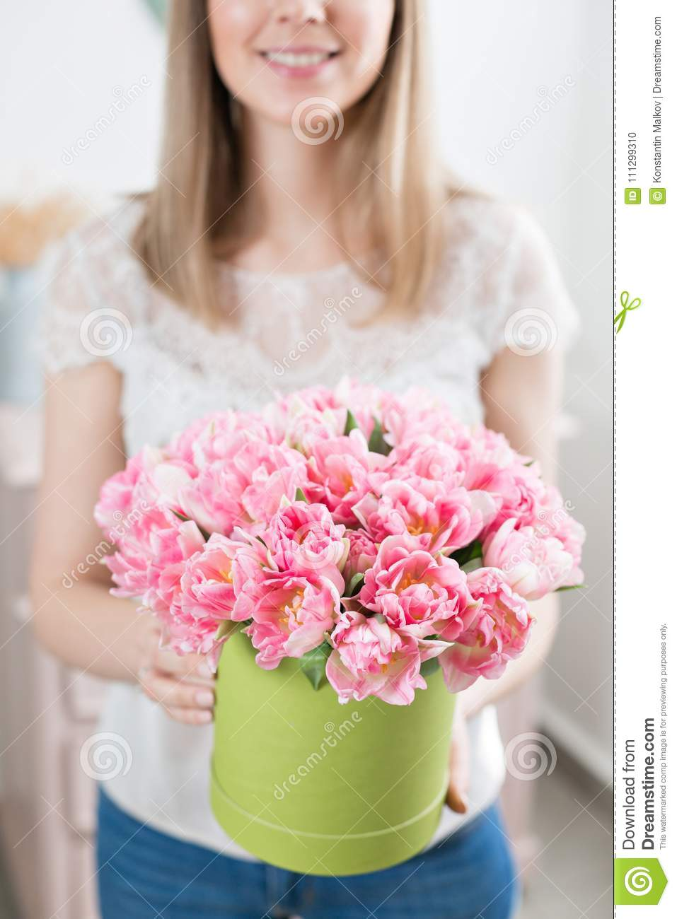 Sunny spring morning young happy woman holding a beautiful bunch of young happy woman holding a beautiful bunch of pink tulips in her hands present for a smiles girl flowers bouquet izmirmasajfo Image collections