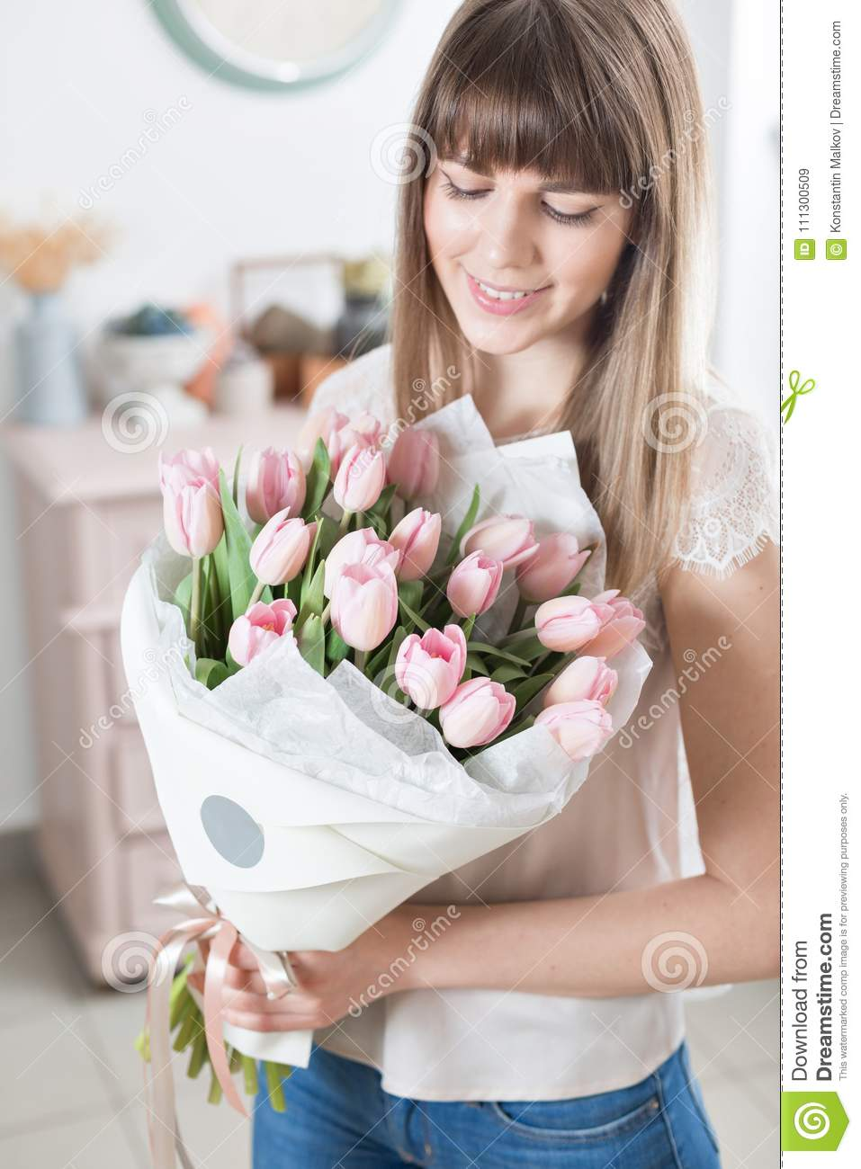 Sunny spring morning. Young happy woman holding a beautiful bunch of pink tulips in her hands. Present for a smiles girl