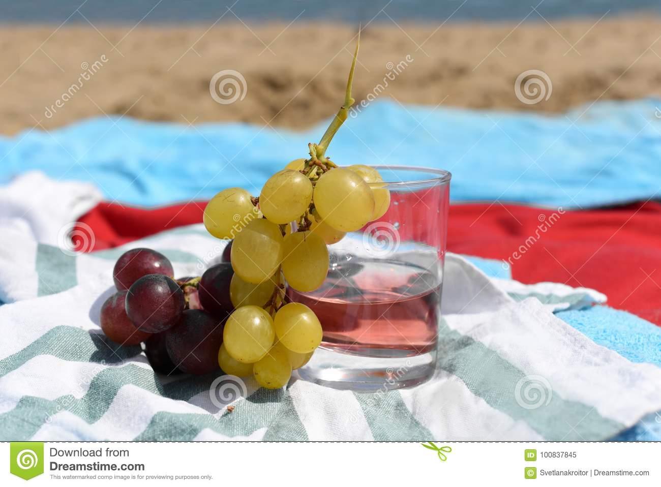 A sunny photo with a glass of wine and grapes against a background of a sand beach and sea