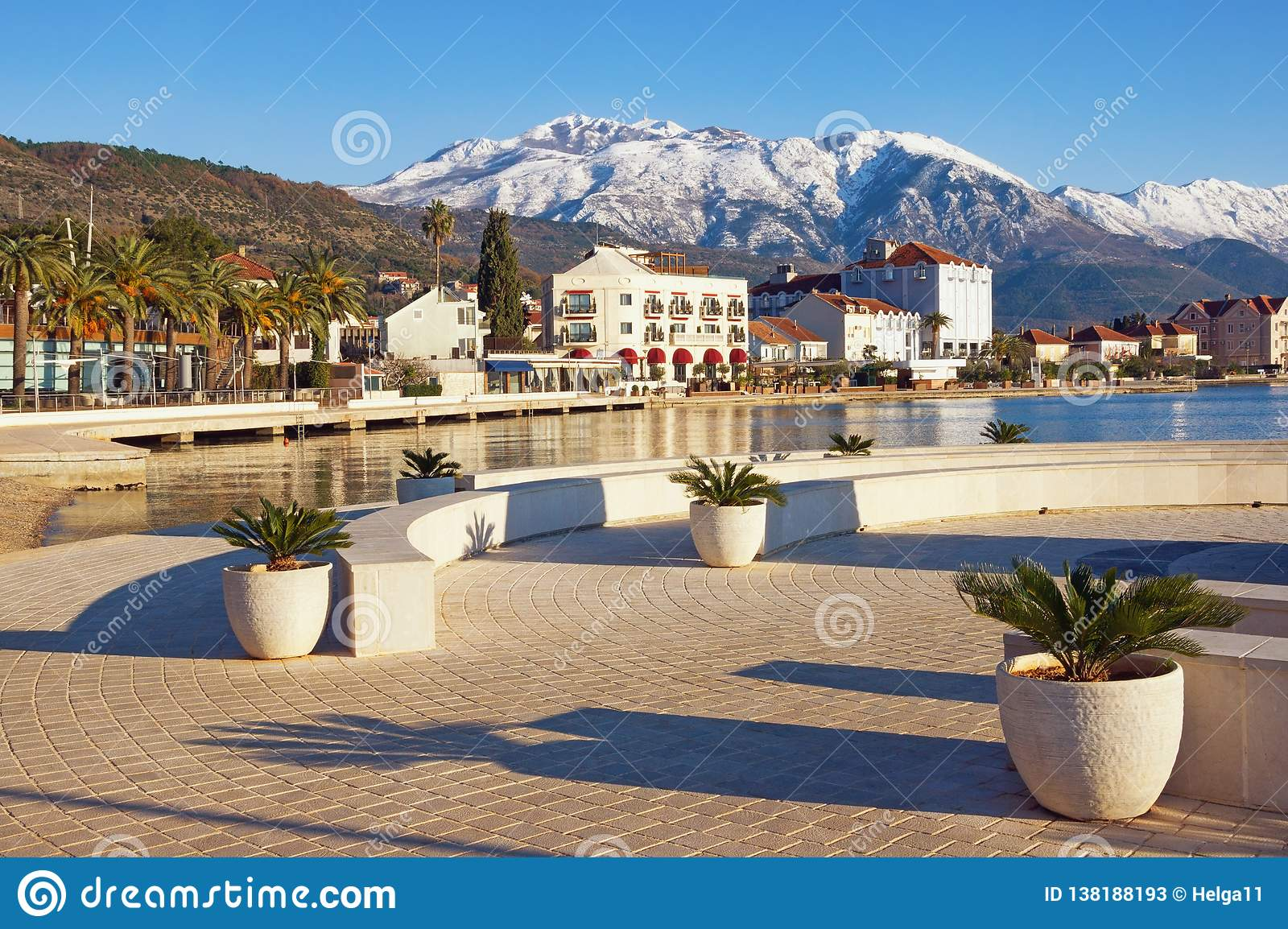 Sunny winter day. Montenegro, view of embankment of Tivat city and snowy peaks of Lovcen mountains