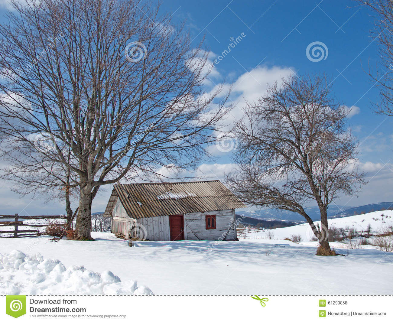 sunny winter day with snow and mountain cottages stock
