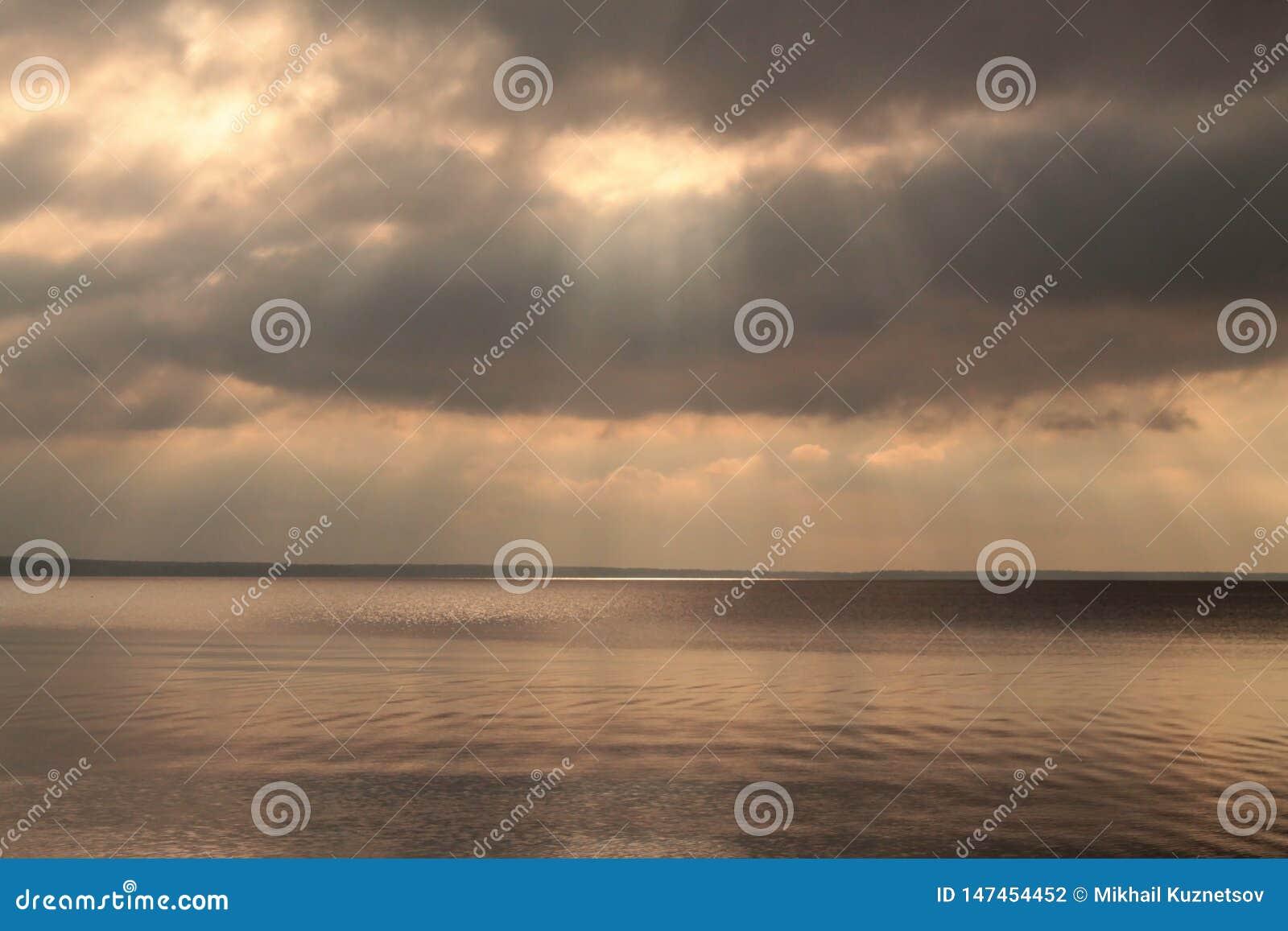 Sunrays przez chmur nad spokojnym jeziorem przed deszczem