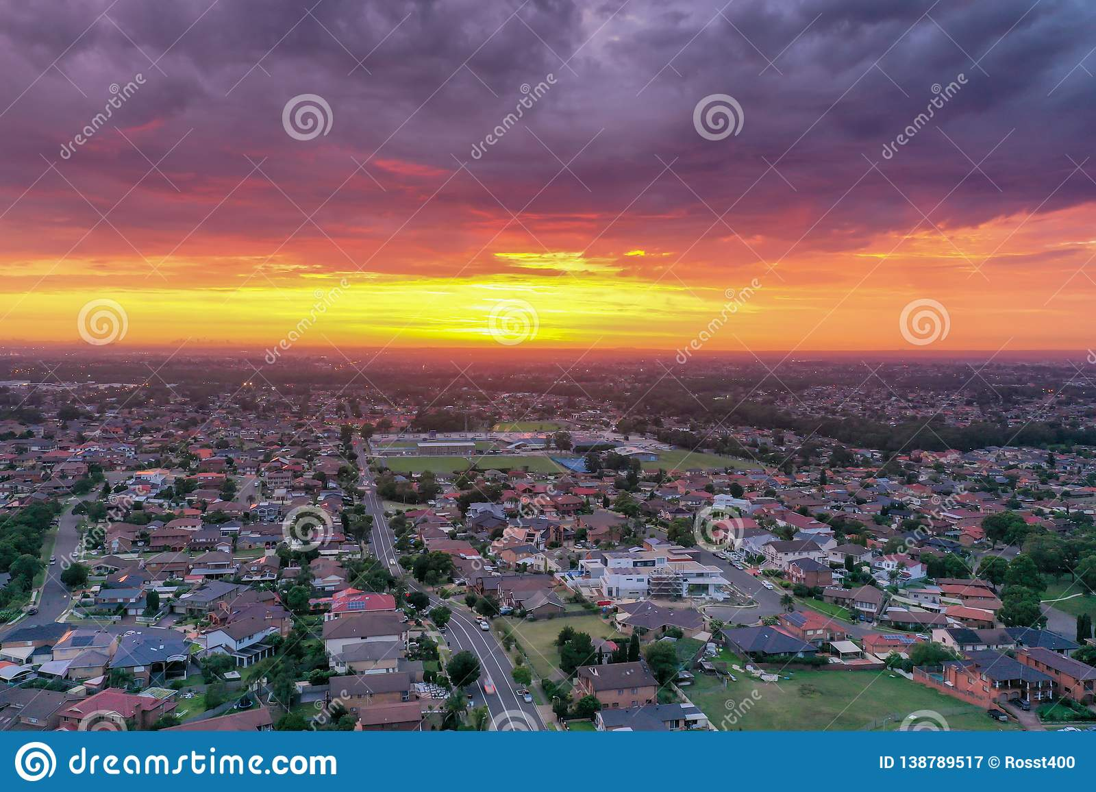 Sunrise above a residential suburbs with streets, homes parks in the background. Dramatic lighting and warm colours