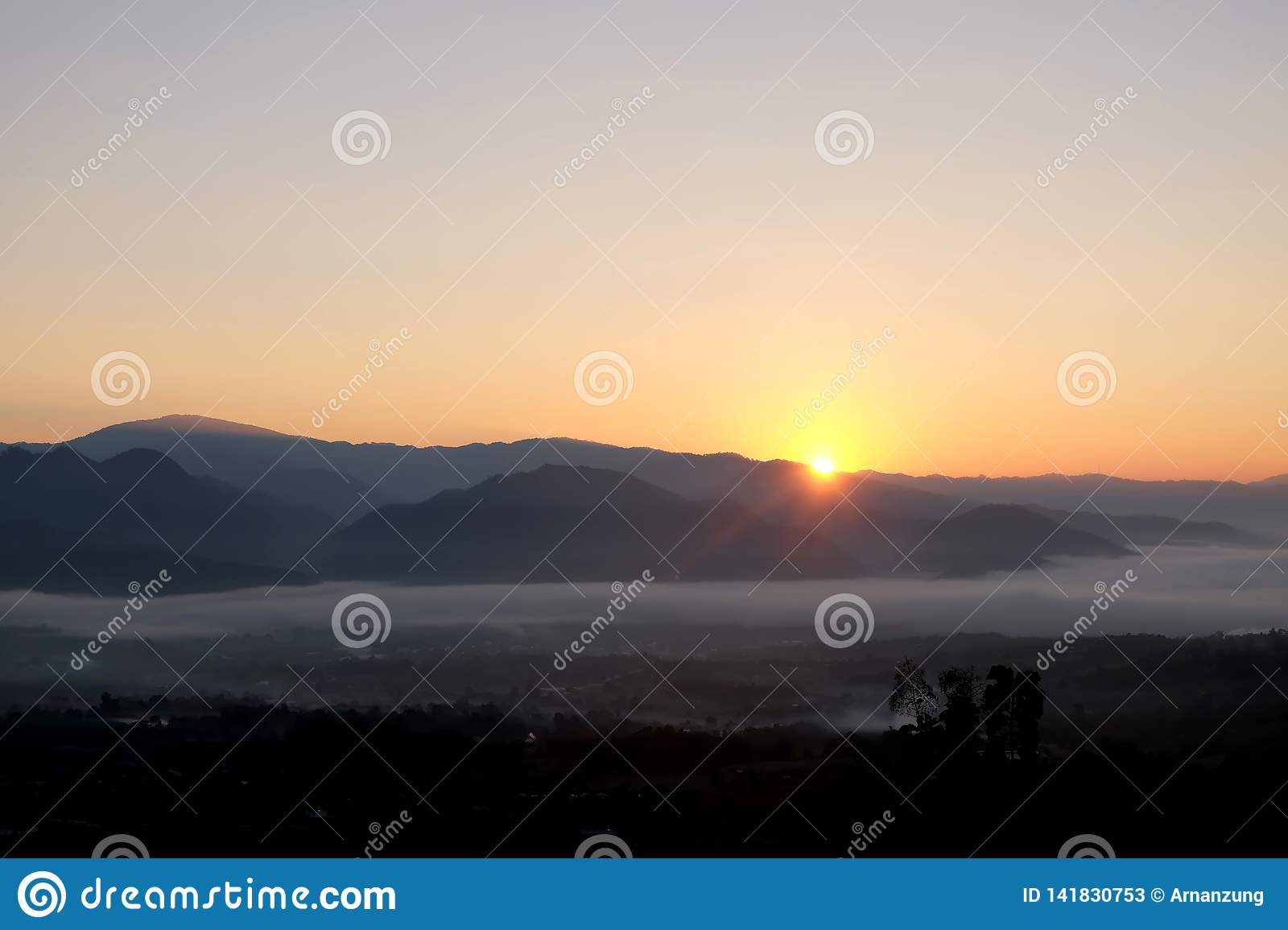 Sunrise behind mountain in the morning with magnificent mist landscape in winter season.