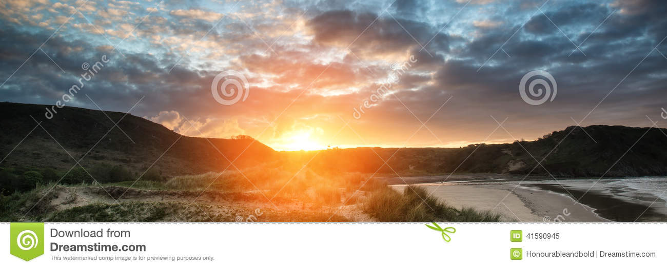 Sunrise landscape panorama Three Cliffs Bay in Wales with dramatic sky