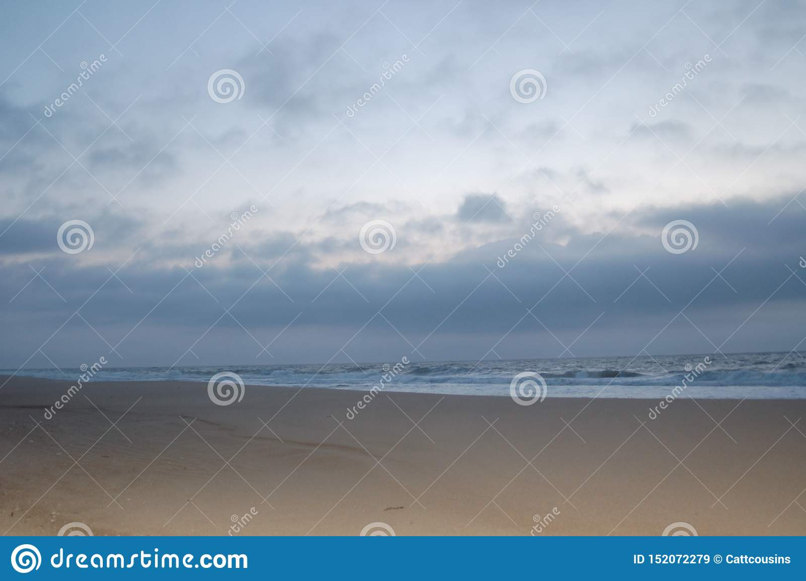 Sunrise on the ocean, white sky, and sand