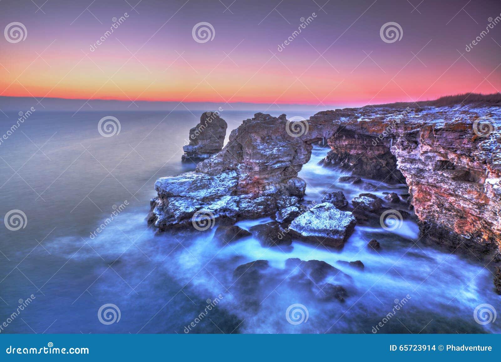 Sunrise over the sea and rocky shore
